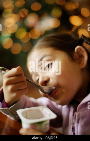 Five year old girl eats yoghurt from pot - Stock Photo