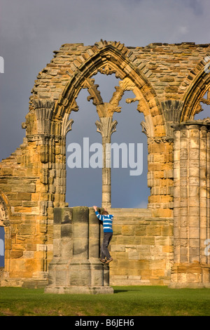Boy climbing in the ruins of Whitby Abbey, North Yorkshire - Stock Photo