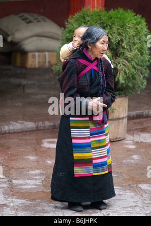 Tibetan grandmother carrying her grandchild, Lhasa, Tibet - Stock Photo
