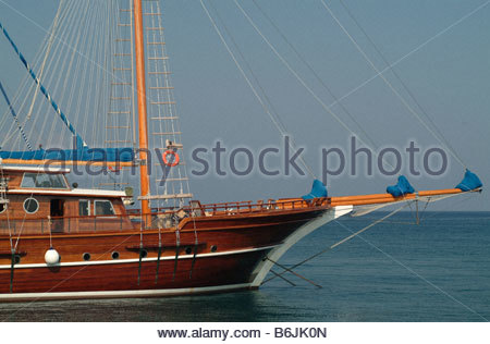 Boat sailboat yacht in the sea blue sky sailing rigging yachts mast wood wooden - Stock Photo
