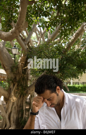 Young man head in hands - Stock Photo