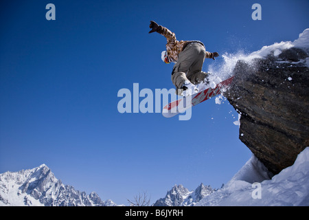 A snowboarder jumps off a rock at Le Brevent, Chamonix, France. - Stock Photo