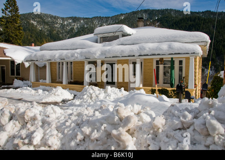 Older house with snow on roof and piled up in front - Stock Photo