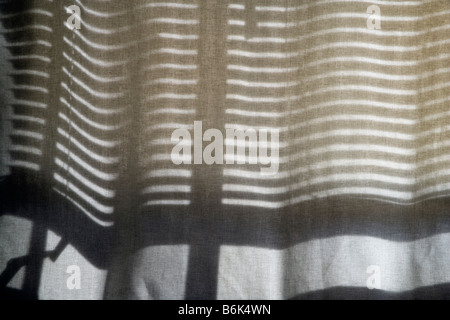 Venetian blinds cast a pattern of shadows on a transparent curtain. - Stock Photo