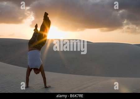 woman doing a handstand on the beach - Stock Photo