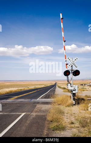 Railroad crossing with gates in New Mexico, USA - Stock Photo