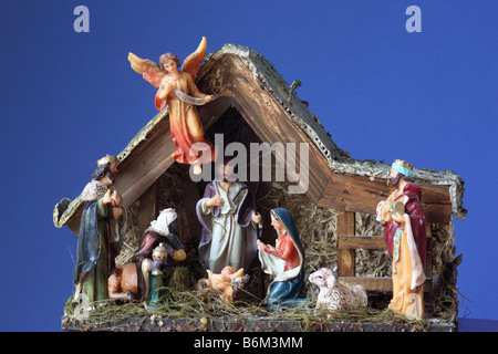 Close up of a Christmas Nativity scene against a plain blue background - Stock Photo