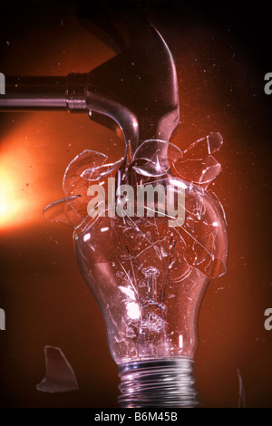 Conventional incandescent light bulb crushed by hammer - Stock Photo