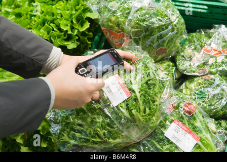 young woman scans the price of a packaged salad into her cell phone in the real Future store part of the Metro Group - Stock Photo