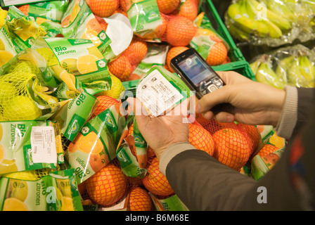 young woman scans the price of packaged fruit into her cell phone in the real Future store part of the Metro Group - Stock Photo