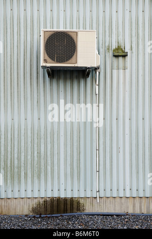 Air conditioning unit on exterior corrugated wall - Stock Photo