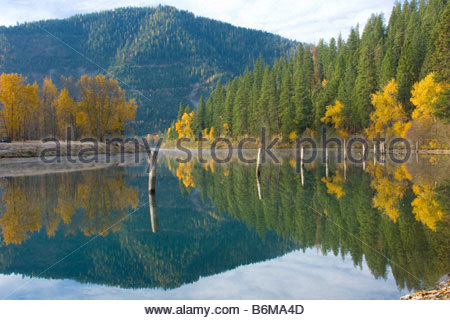 Idaho Rose Lake Reflections in the water with rising mist and autumn colors - Stock Photo