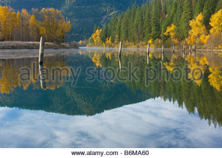 Reflections in the water of the Coeur d Alene River with rising mist, pilings and autumn colors. - Stock Photo