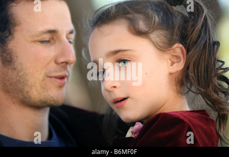 A father holding his 7 year old daughter - Stock Photo