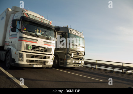 Two articulated lorries overtaking on the M25 - Stock Photo