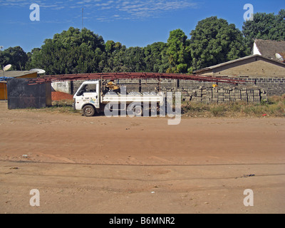 Roof trusses being loaded on a small van in The Gambia, West Africa - Stock Photo