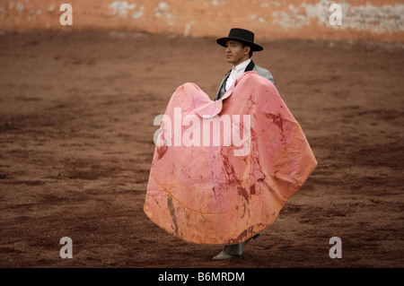 A bullfighter holds a cape splattered with blood as he waits for a bull to charge during a bullfight in Mexico City - Stock Photo