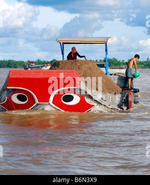 Brightly coloured red river boat carrying topsoil,  Tien Giang River, Mekong Delta, Vietnam - Stock Photo