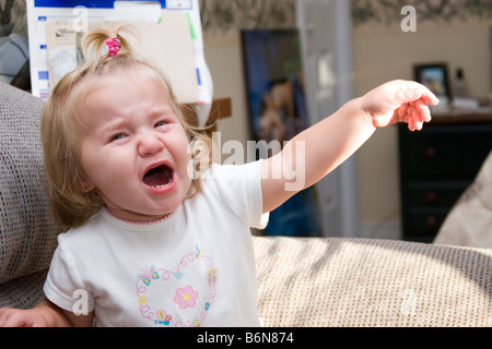 1 to 2 year old toddler girl upset and crying having tantrum - Stock Photo