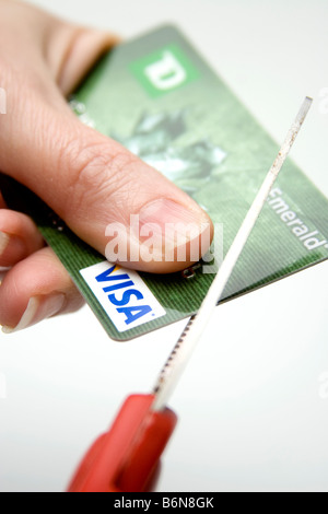 Concept of hand holding a visa credit card while scissors cuts it up symbolizing lean times - Stock Photo