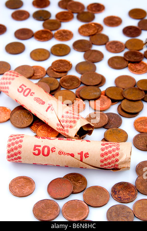 Concept of paper coin rollers amoung pennies on white background symbolizing lean times - Stock Photo