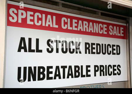 Sign across a full shop window on a high street in Belfast UK all stock reduced unbeatable prices special clearance - Stock Photo