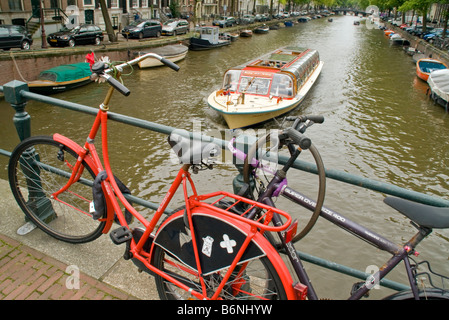 Amsterdam bikes locked to bridge with sightseeing cruise boat in Prinsengracht canal - Stock Photo