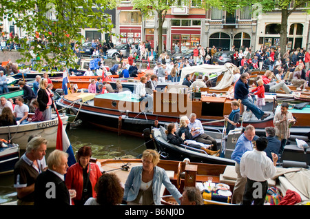 Amsterdam crowd in boats at free open air summer festival of classical music concerts on Prinsengracht Canal - Stock Photo