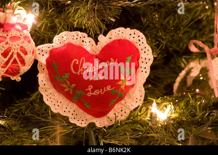 Handmade Christmas tree heart ornament with 'Christmas Is Love' written in the center - Stock Photo
