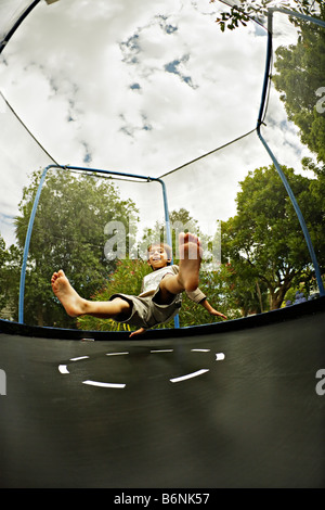 Six year old boy on tampoline - Stock Photo