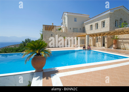 Luxury villa and exclusive private infinity pool overlooking Crete and Aegean sea with palms and typical grecian - Stock Photo