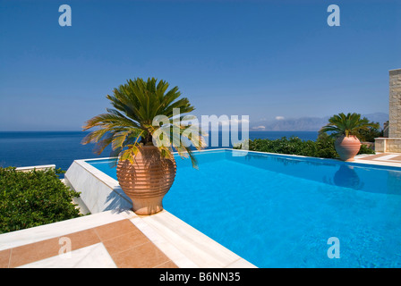 Luxury exclusive private infinity pool inviting a dip, overlooking Aegean sea with palms and typical grecian urns - Stock Photo