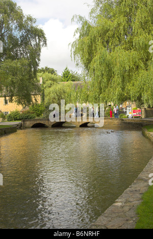 The River Windrush flowing through the picturesque Cotswold village of Bourton-on-the-Water, Gloucestershire. - Stock Photo