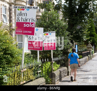 Woman walking past three for sale house signs with sale sold to let Cardiff Wales UK - Stock Photo