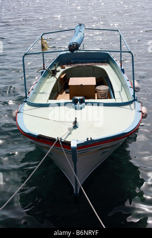 small wooden fishing boat anchored - Stock Photo