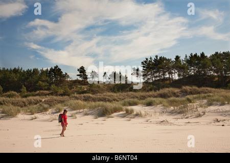 Woman walking on beach with marram grass on sand dunes Slowinski national park Poland - Stock Photo