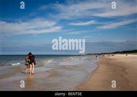 Couple walking in shallows of Baltic Sea Slowinski national park Poland - Stock Photo