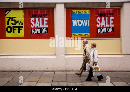 Signs announce the start of the January sales on a British high street. - Stock Photo