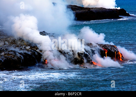 Image of molten lava flowing down the hill and into the sea while steam rises all around - Stock Photo