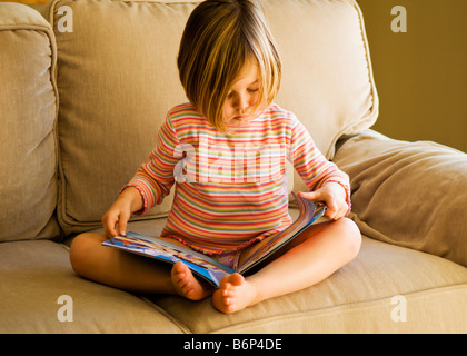 Girl, 3-5 years, sits on a cozy sofa reading a book. - Stock Photo