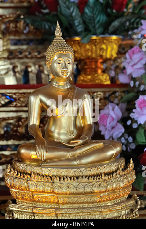 Buddha statue with pink roses in buddhist temple in Bangkok's chinatown, Thailand - Stock Photo