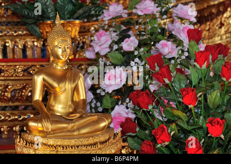 Buddha statue with red and pink roses in buddhist temple in Bangkok's chinatown, Thailand - Stock Photo