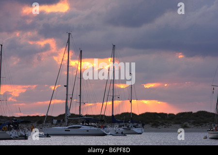 The sun rises among the clouds behind the ships anchored in the island of Espalmador, a small island in the Balearic - Stock Photo