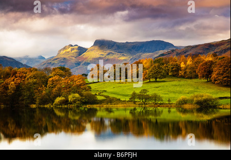 Autumn view over Loughrigg Tarn Lake District National Park Cumbria England UK with the Langdale Pikes in the distance