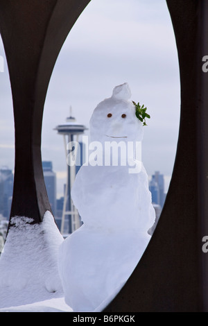 Snowman built inside metal sculpture Changing Form by Doris Totten Chase at Kerry Park on Queen Anne Hill Seattle - Stock Photo