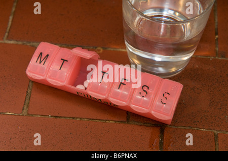 pill dispenser containing a person s medication for 7 days with a glass of water - Stock Photo