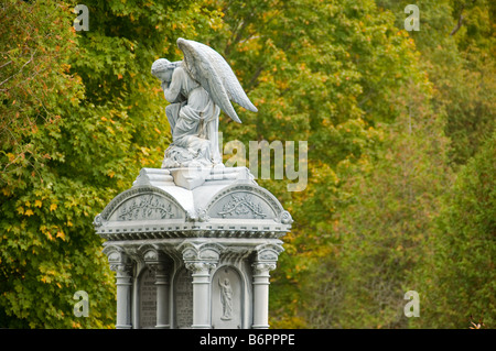 Statue of an angel in a cemetery with out of focus trees in the background - Stock Photo