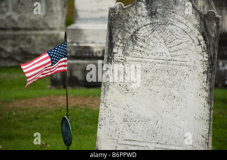 US flag next to a headstone in an old graveyard - Stock Photo