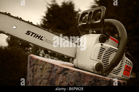 Chainsaw posed on cut tree stump. - Stock Photo