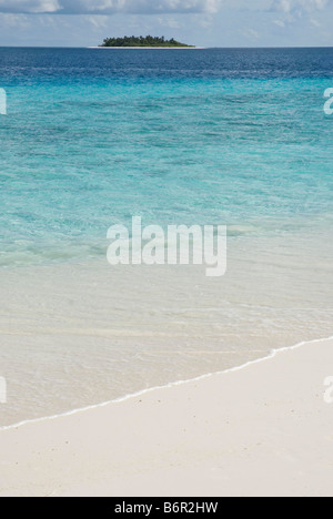 Small uninhabited tropical island in the Maldives and sand and turquoise coloured shallow water in the foreground. - Stock Photo